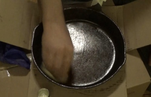 Rubbing restored cast iron frying pan with oil